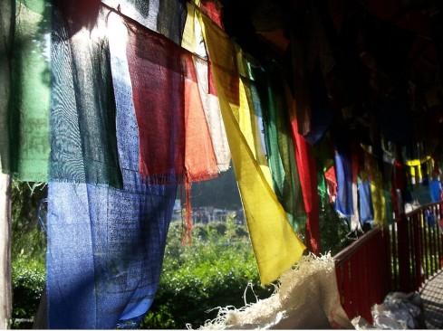 sunlight filtering in through prayer flags at Tso Pema